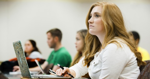 girl with other students in class listening to professor